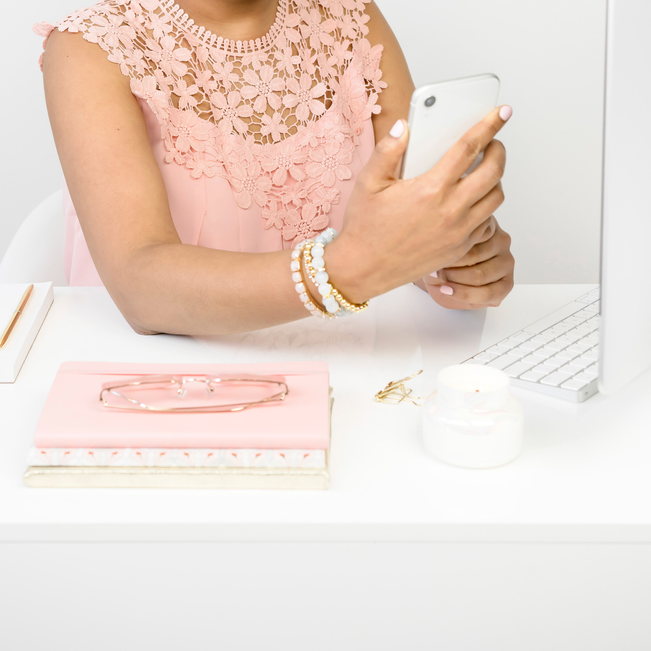 women holding phone wearing pink at a white desk